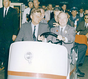 President John F. Kennedy and CEO James S. McDonnell tour the McDonnell Aircraft factory in 1962 aboard McDonnell's modified Cushman golf cart