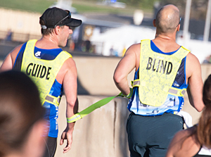 Nick Abramczyk, a Boeing employee, guides Thomas Panek, a blind runner, along the course of the Army Ten Miler