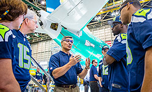 Ray Conner (center), president and CEO of Commercial Airplanes, leads Seattle Seahawks teammates Cliff Avril (second from right) and Malcolm Smith (right) on a tour