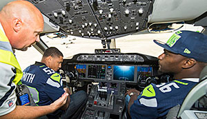 Tom Meier (left), a Boeing Test & Evaluation flight-test manufacturing manager, explains the intricacies of the 787-9 flight deck to Seahawks teammates Malcolm Smith (center) and Cliff Avril