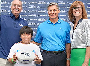 (From left) Steve Raible, Seahawks radio announcer, poses with Boys & Girls clubs member Johnny Tran, Ray Conner, president and CEO of Boeing Commercial Airplanes and Linda Nageotte, president and CEO of Food Lifeline
