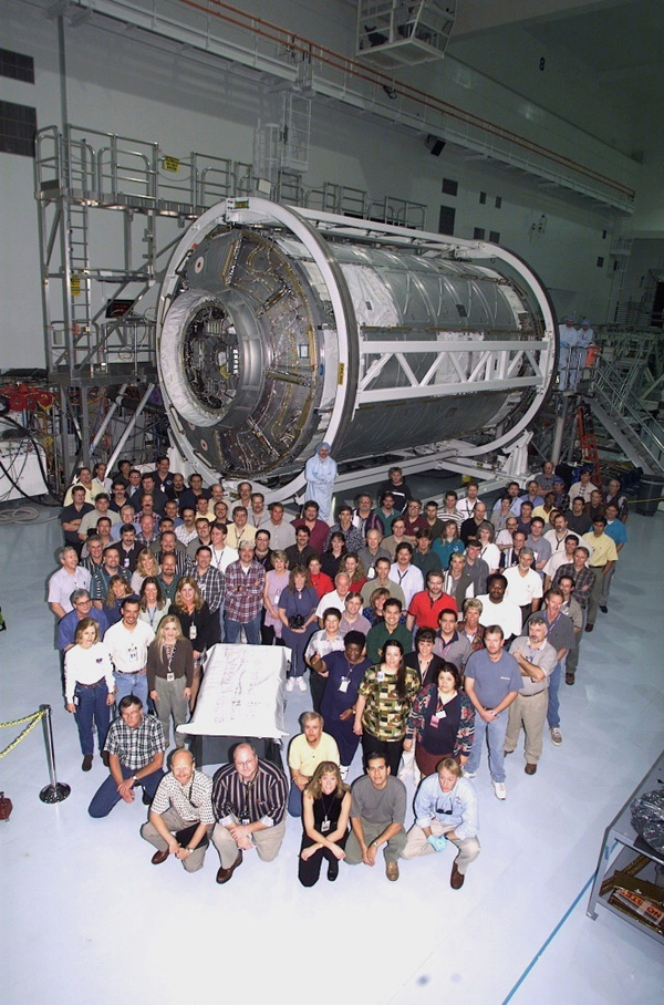 Kennedy Space Center workers standing with International Space Station Lab