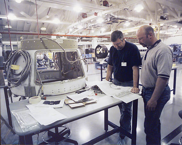 Boeing technicians review procedures for routing cables in the aft-skirt of the ground-based interceptor.