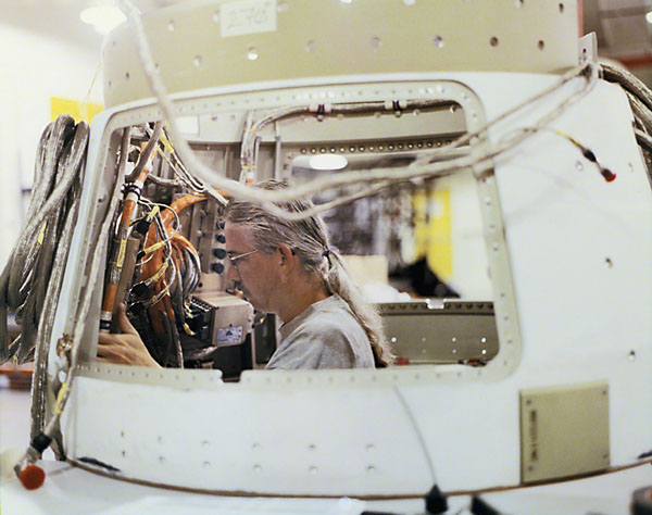 Boeing technician, Cliff Wagner, routes cable while working on electronics in the aft-skirt of the ground-based interceptor.