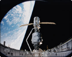 In December 1998, the crew of Space Shuttle Mission STS-88 began construction of the International Space Station, joining the U.S.-built Unity node to the Russian-built Zarya module. The crew carried a large-format IMAX  camera from which this picture was taken. - Astronauts Ross (left) and Newman looking over work completed on Zarya and Unity.