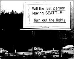 Billboard by highway reading 'last person leaving Seattle - turn out the lights'