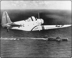 TBD Devastator torpedo bomber in flight over aircraft carrier
