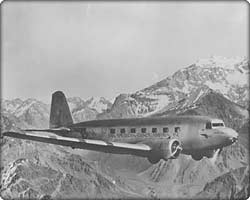 DC-2 commercial transport in flight over mountains