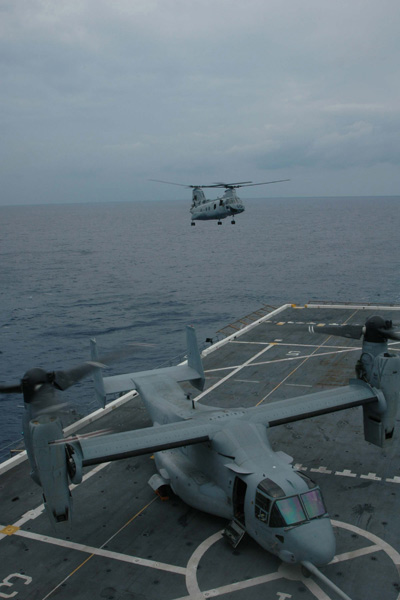 A CH-46 Sea Knight helicopter prepares to land near a V-22 Osprey tiltrotor aircraft aboard the amphibious transport dock USS San Antonio (LPD 17) June 5, 2006.  The ship is under way in the Atlantic Ocean testing the capabilities of both aircraft to determine their compatibility with the Navy's new