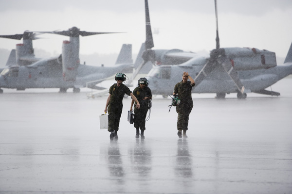 Three military soldiers in front of several V-22.