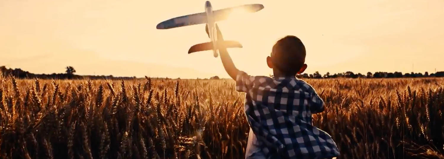 Picture of a boy flying a toy plane in a field of wheat at sunrise.